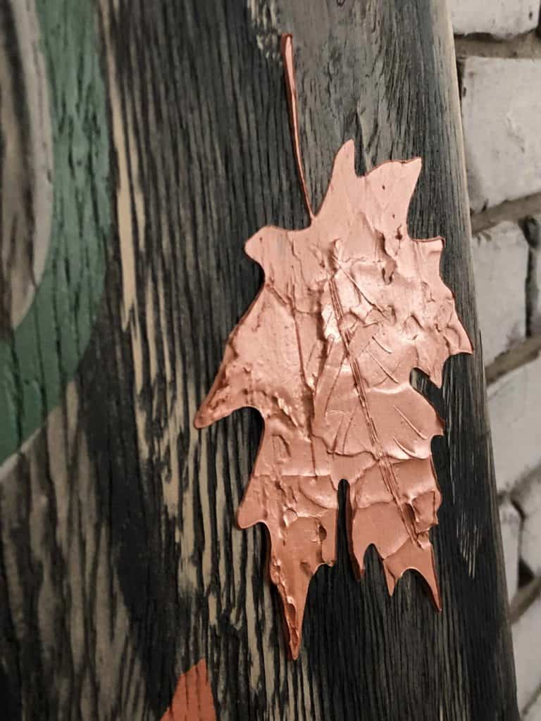 Embossed leaf stencil on Autumn sign.